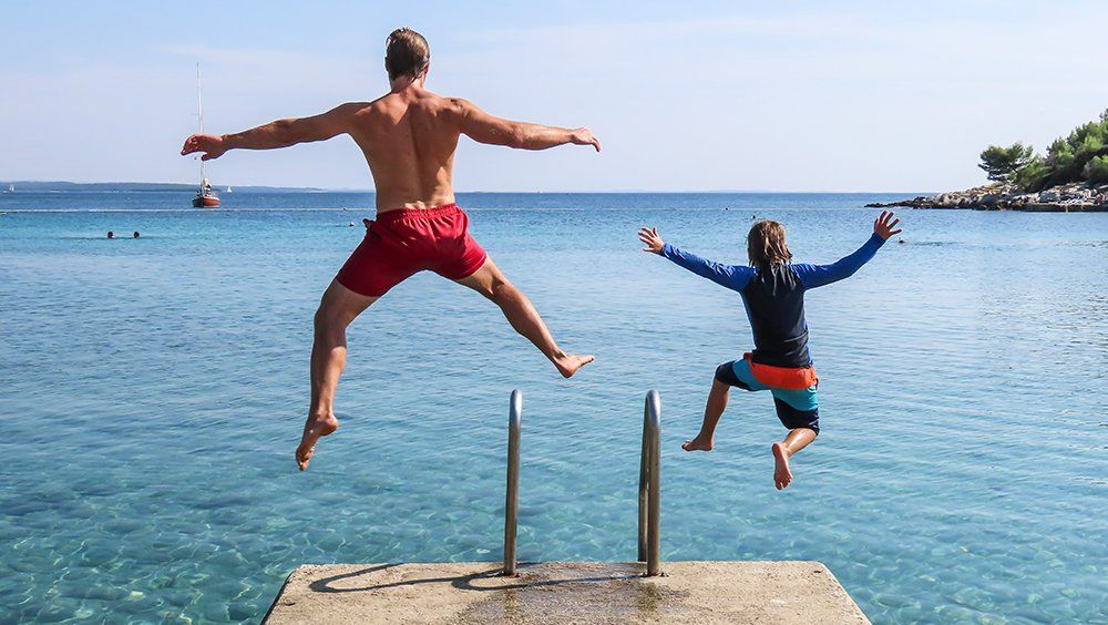 Father and Son jumping in to bright blue sea